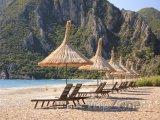 Lehátka se slunenčníky na pláži