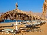 Slunečníky a lehátka na pláži rezortu Nuweiba
