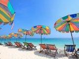 Barevné slunečníky a lehátka na pláži